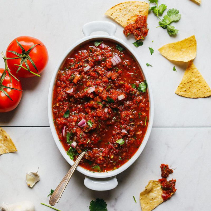 Tortilla chips and tomatoes around a dish of homemade salsa for an Easy New Year's Snack idea