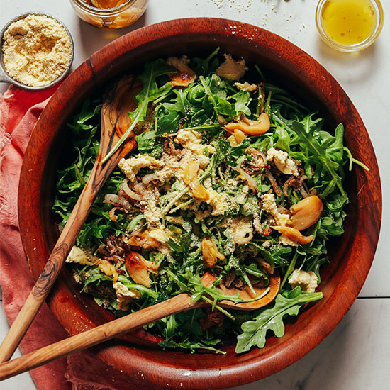 Salad spoons in a big wood bowl filled with Arugula Salad with Crispy Shallots