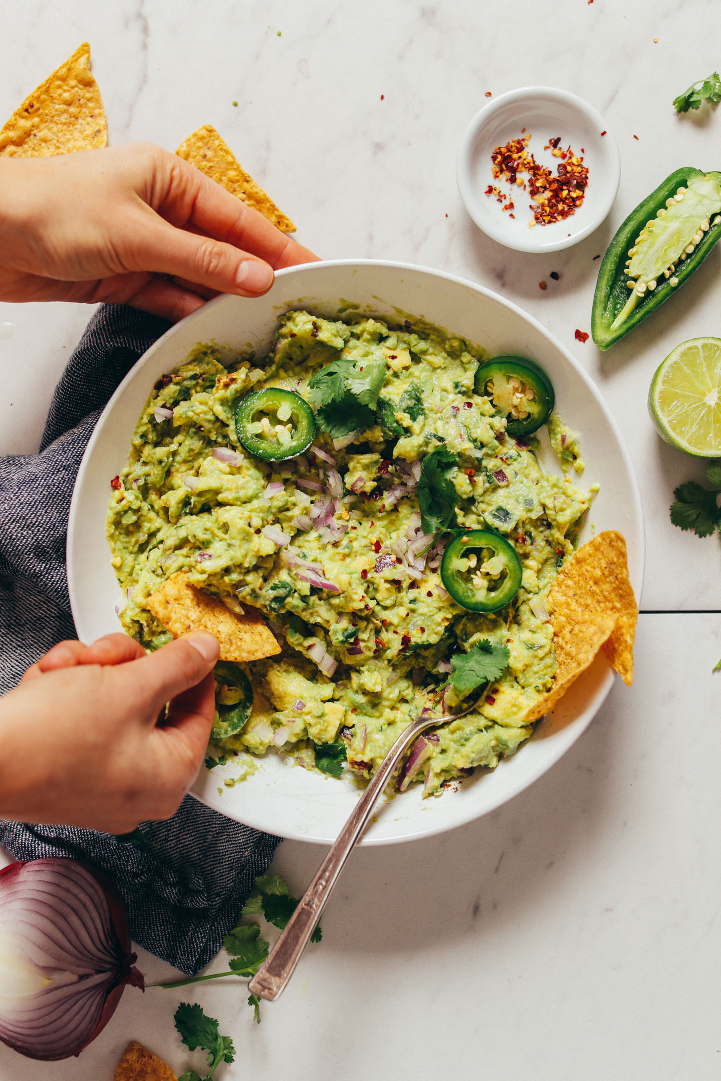 Overhead image of guacamole in a white bowl garnished with fresh jalapenos, and a hand with a chip scooping some guacamole