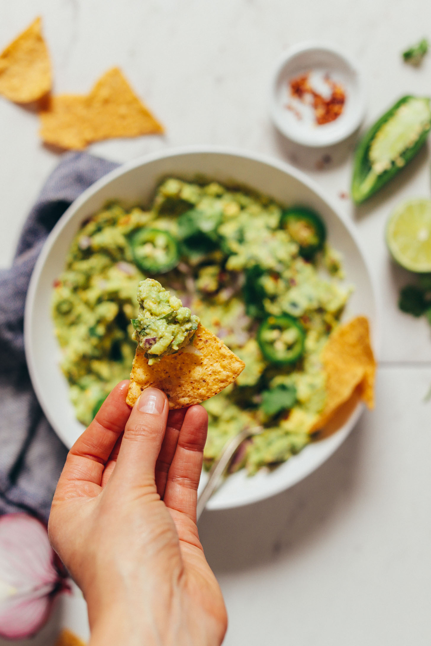 An overhead image of guacamole in a white bowl in the background with a hand holding a chip with some guacamole in focus overhead