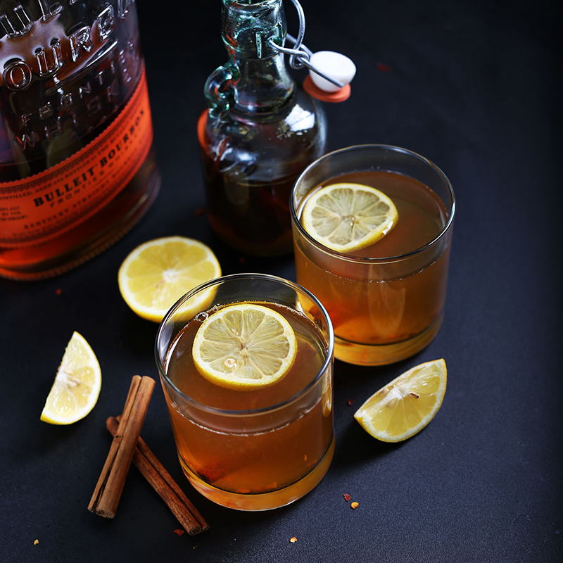 Glasses of our Chili Cinnamon Hot Toddy topped with lemon slices