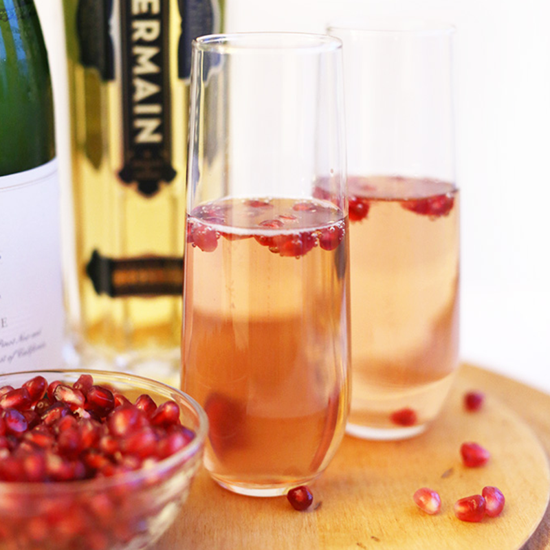 Pomegranate seeds in a bowl beside two St Germain Spritzers for a festive New Year's Drink