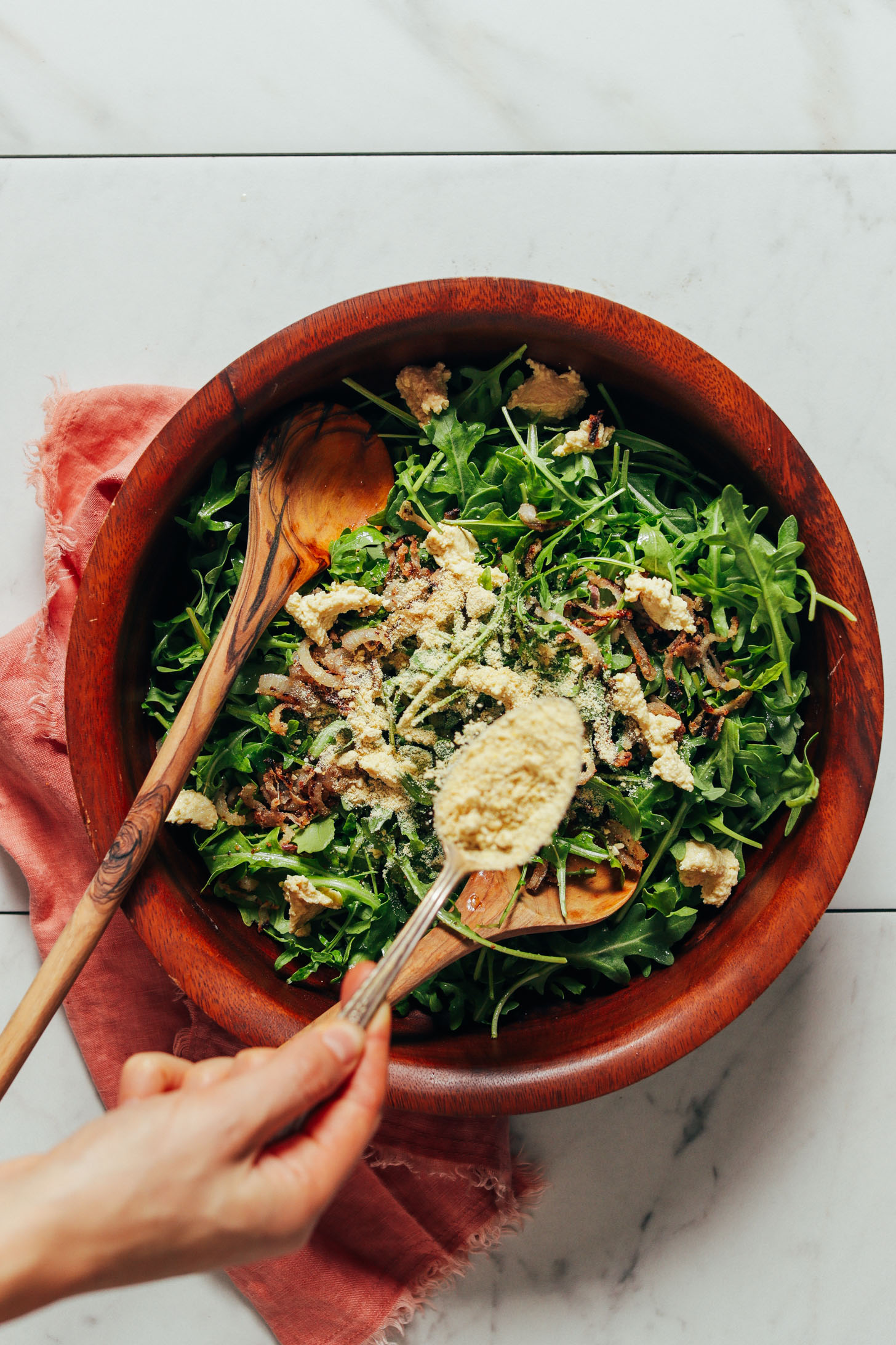 Sprinkling cashew parmesan cheese onto a big bowl of our Lemony Arugula Salad with Crispy Shallot recipe
