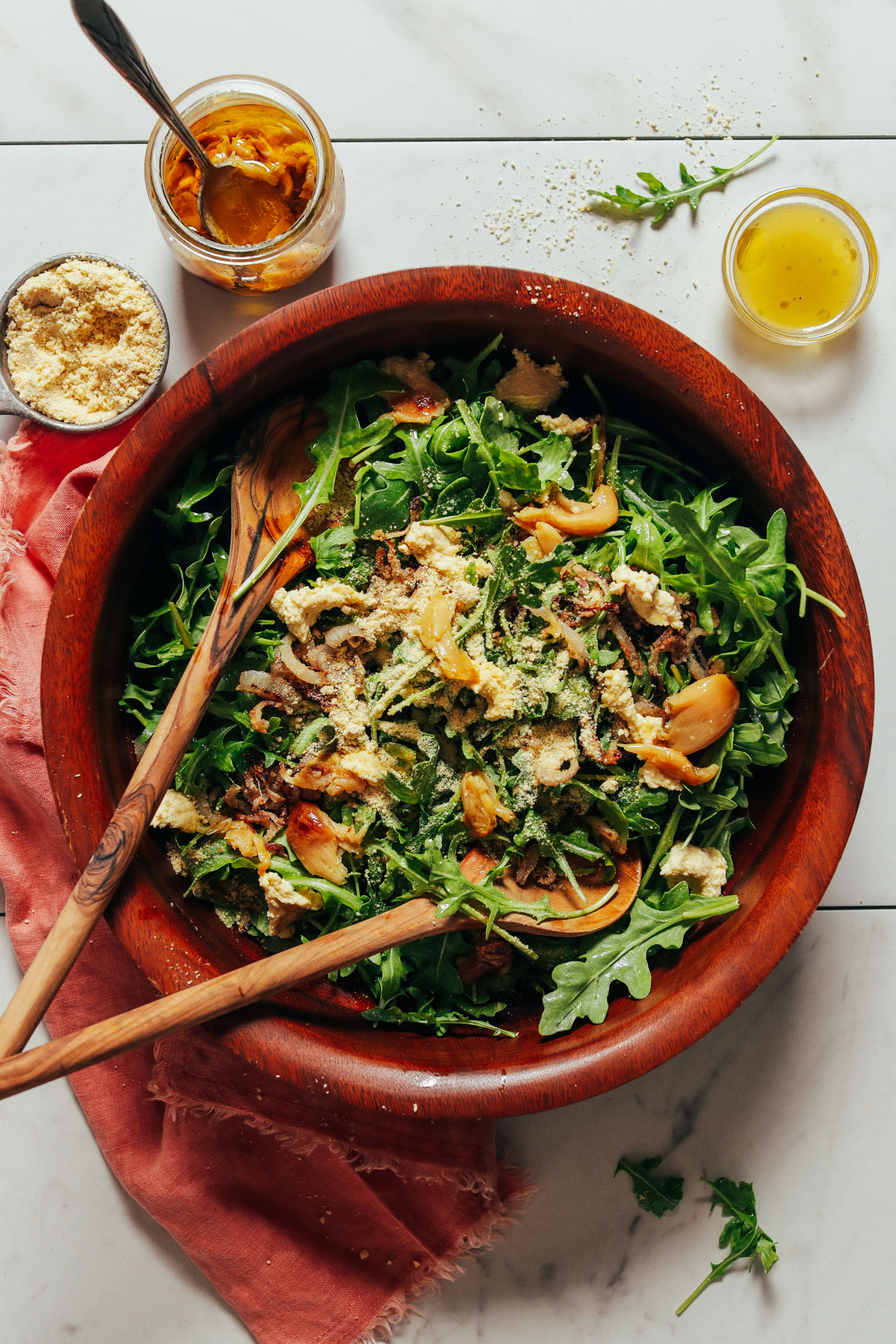Big salad bowl filled with our Lemony Arugula Salad recipe surrounded by ingredients used to make it