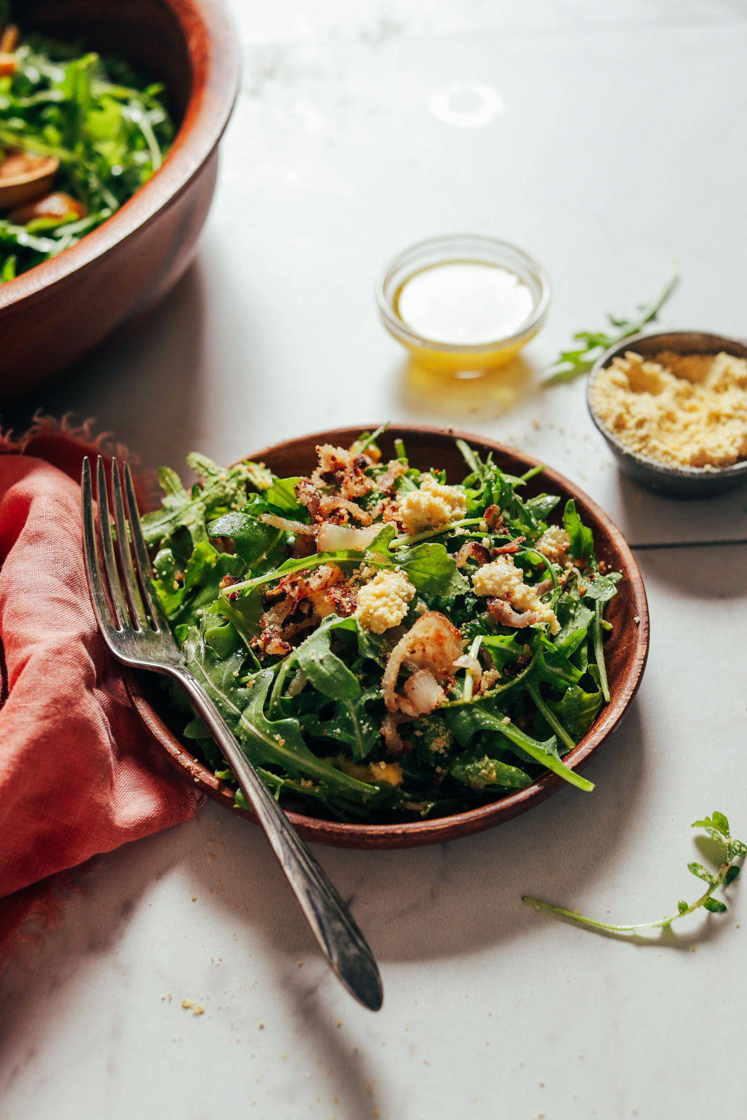 Wooden salad plate with a serving of our Lemony Arugula Salad with Crispy Shallot recipe
