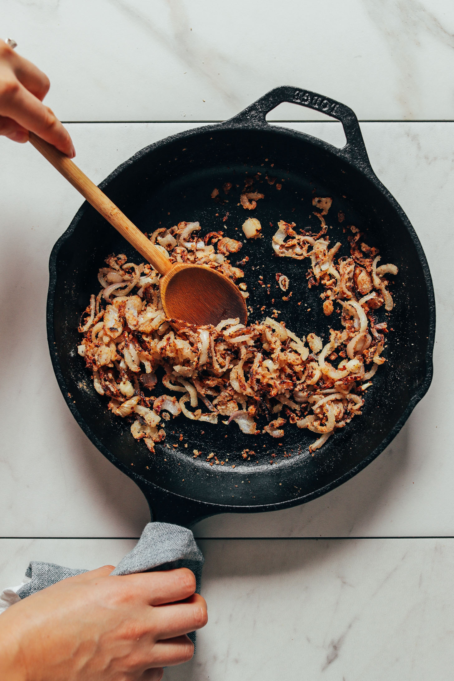 Cooking crispy shallots in a cast iron skillet for our Lemony Arugula Salad recipe