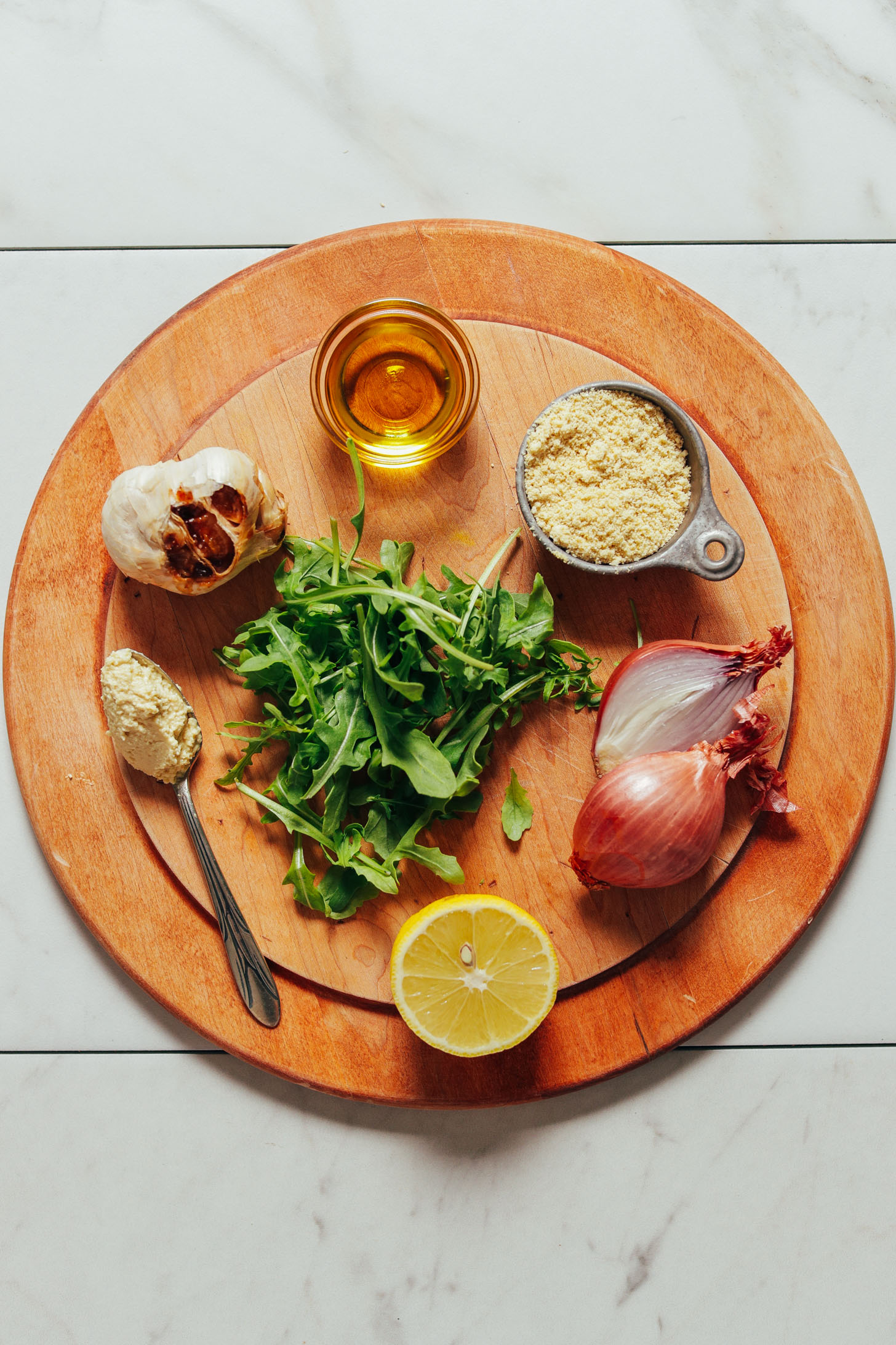 Wood cutting board with arugula, shallots, garlic, lemon, and other ingredients to make our simple Lemony Arugula Salad with Crispy Shallot recipe