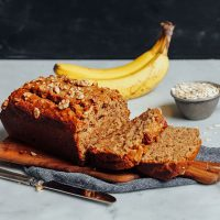Partially sliced loaf of Vegan Gluten-Free Banana Bread with bananas and oats in the background