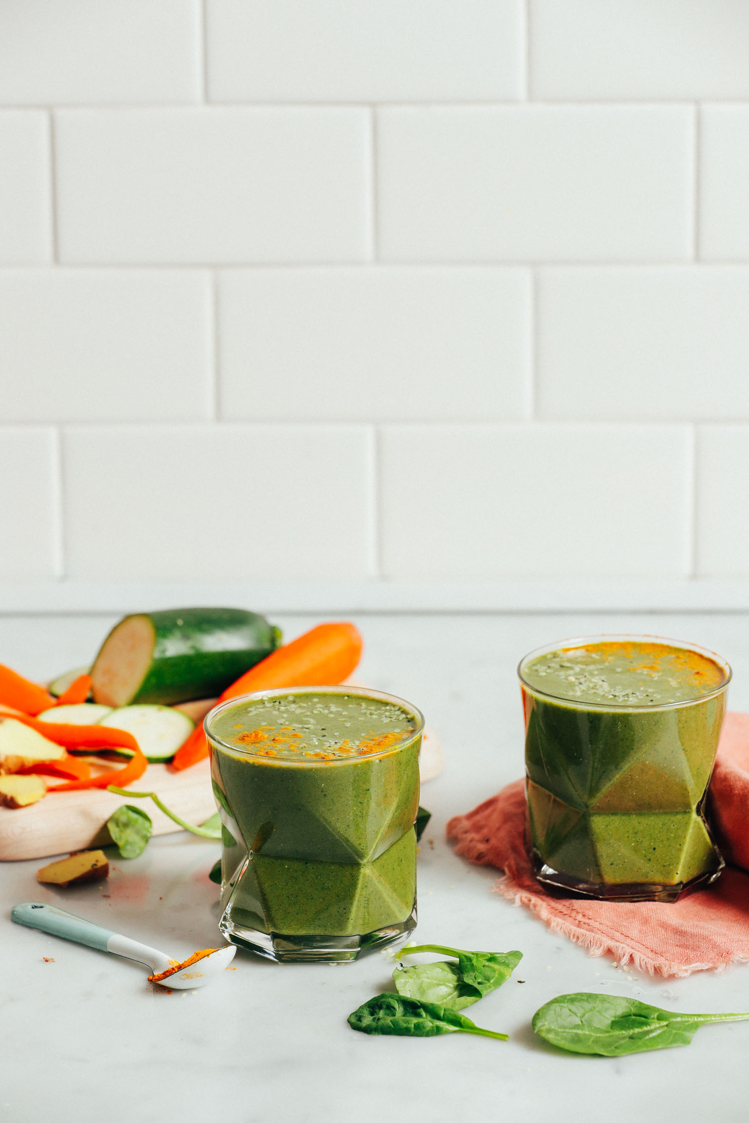 Straight on image of two glasses of warming winter green smoothie with carrot, zucchini, spinach, and turmeric garnish