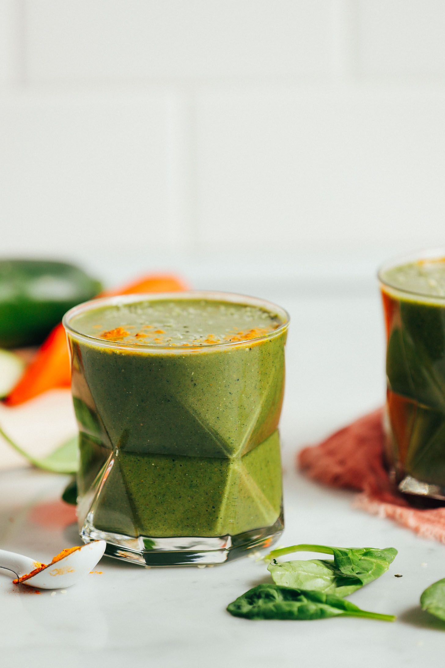 Straight on image of warming winter green smoothie in a glass with carrot, zucchini, and ground turmeric on the side