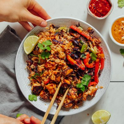 Using chopsticks to grab a bite of our 20-Minute Tofu Stir Fry recipe