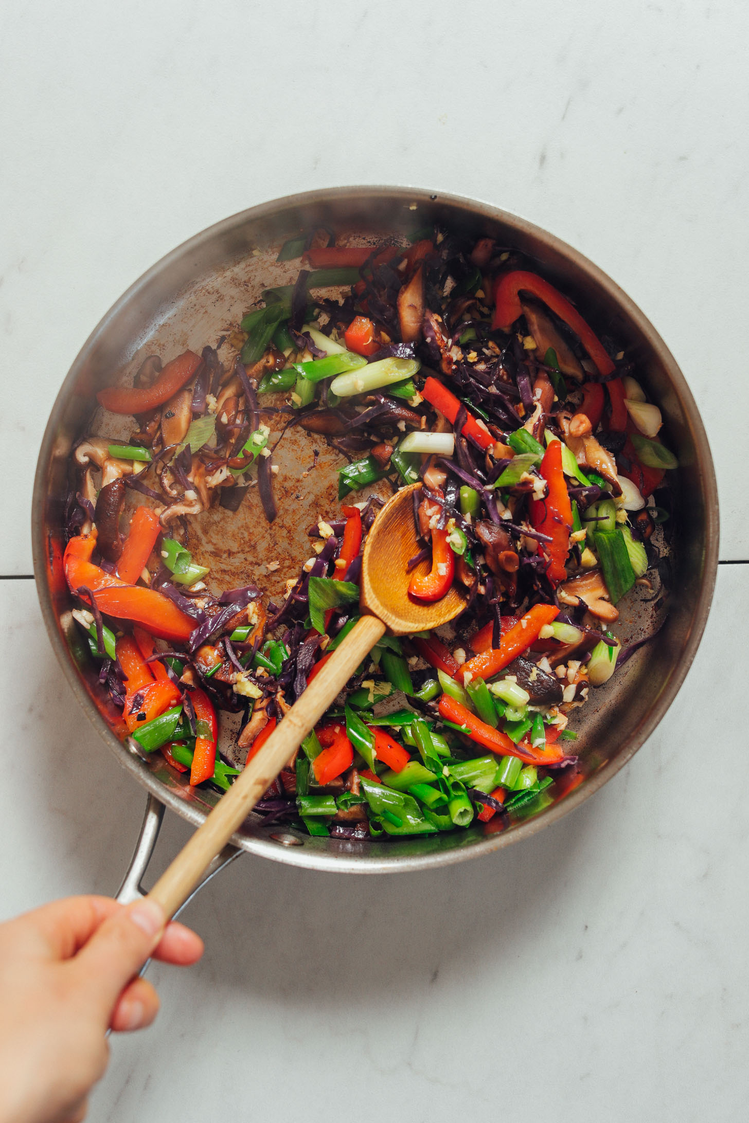 Using a wooden spoon to stir vegetables for a quick Tofu Stir Fry
