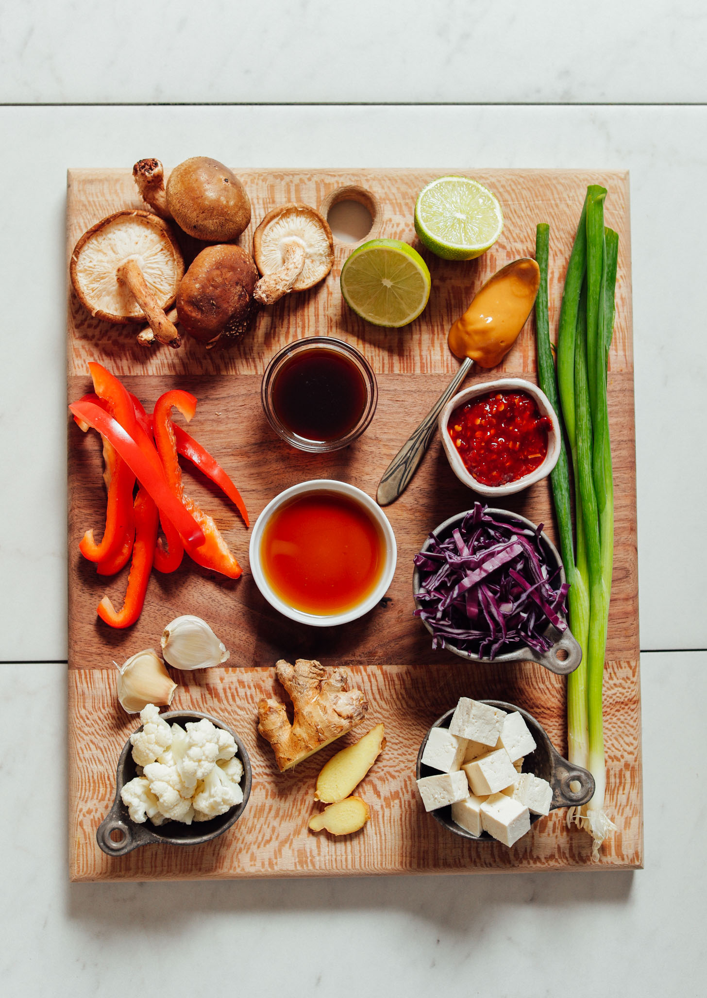 Wood cutting board with ingredients for making our 20-Minute Tofu Stir Fry recipe