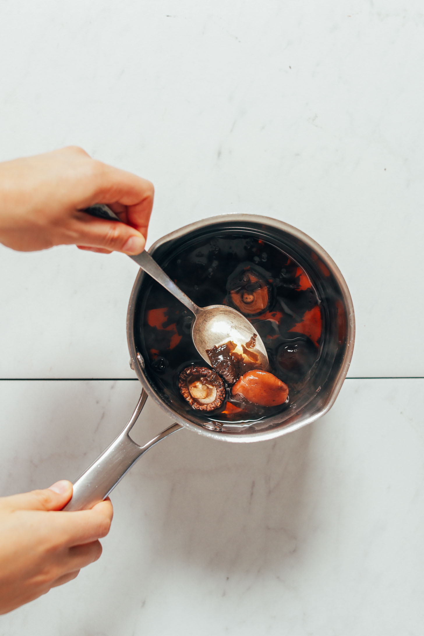 Using a spoon to mix a saucepan with ingredients for our vegetarian Fish Sauce recipe