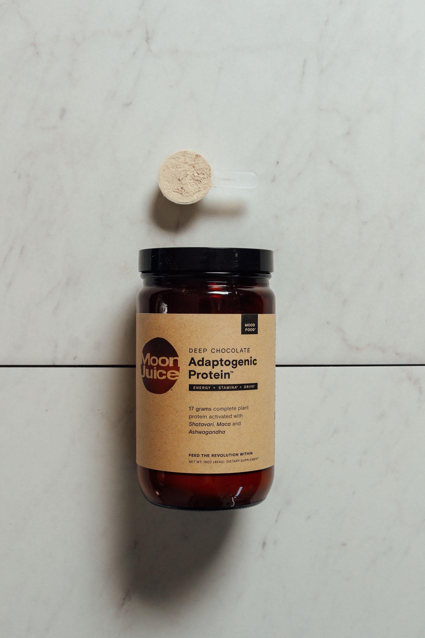 Jar and scoop of Moon Juice Adaptogenic Chocolate Protein Powder