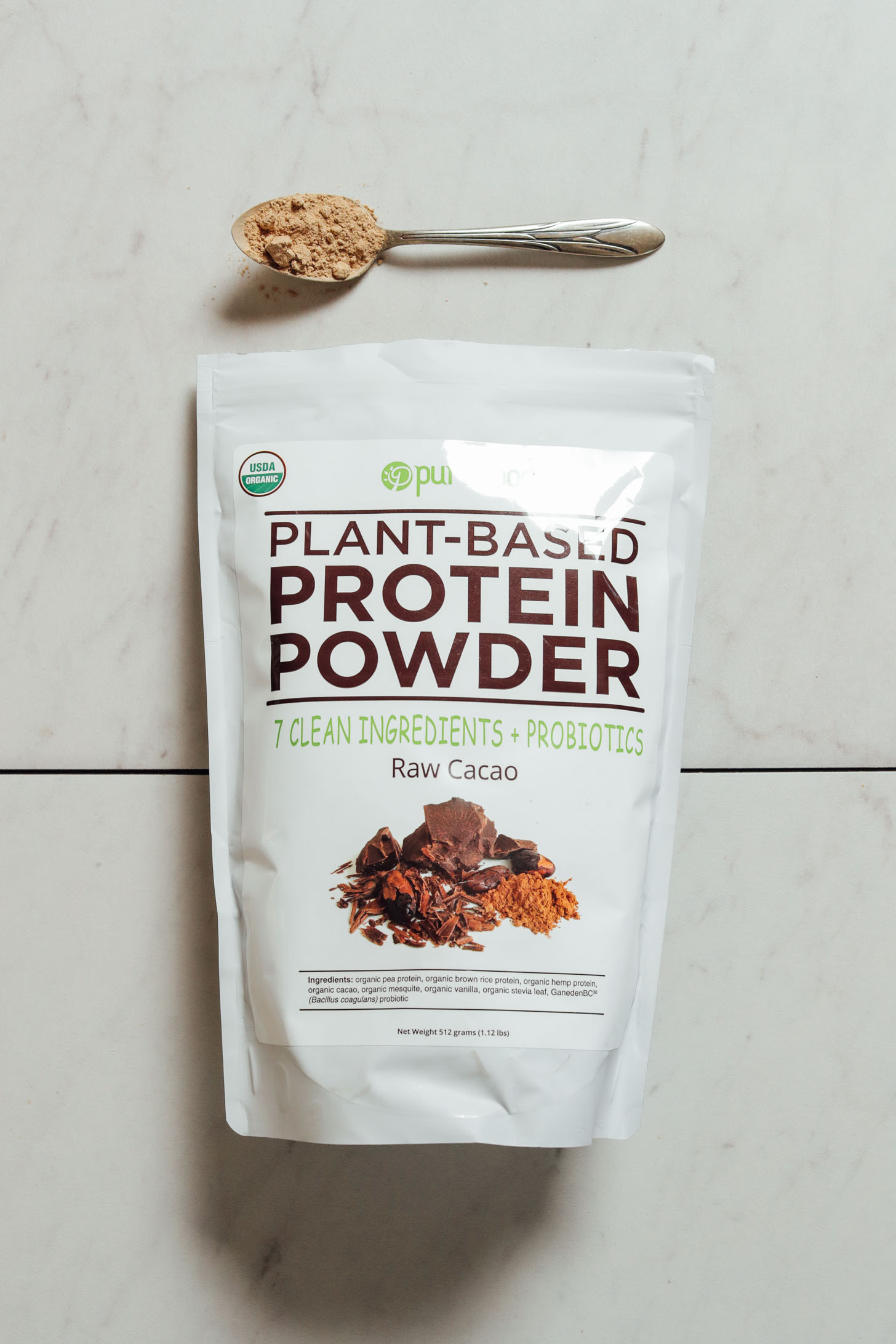 Bag and spoonful of Pure Food Chocolate Protein Powder