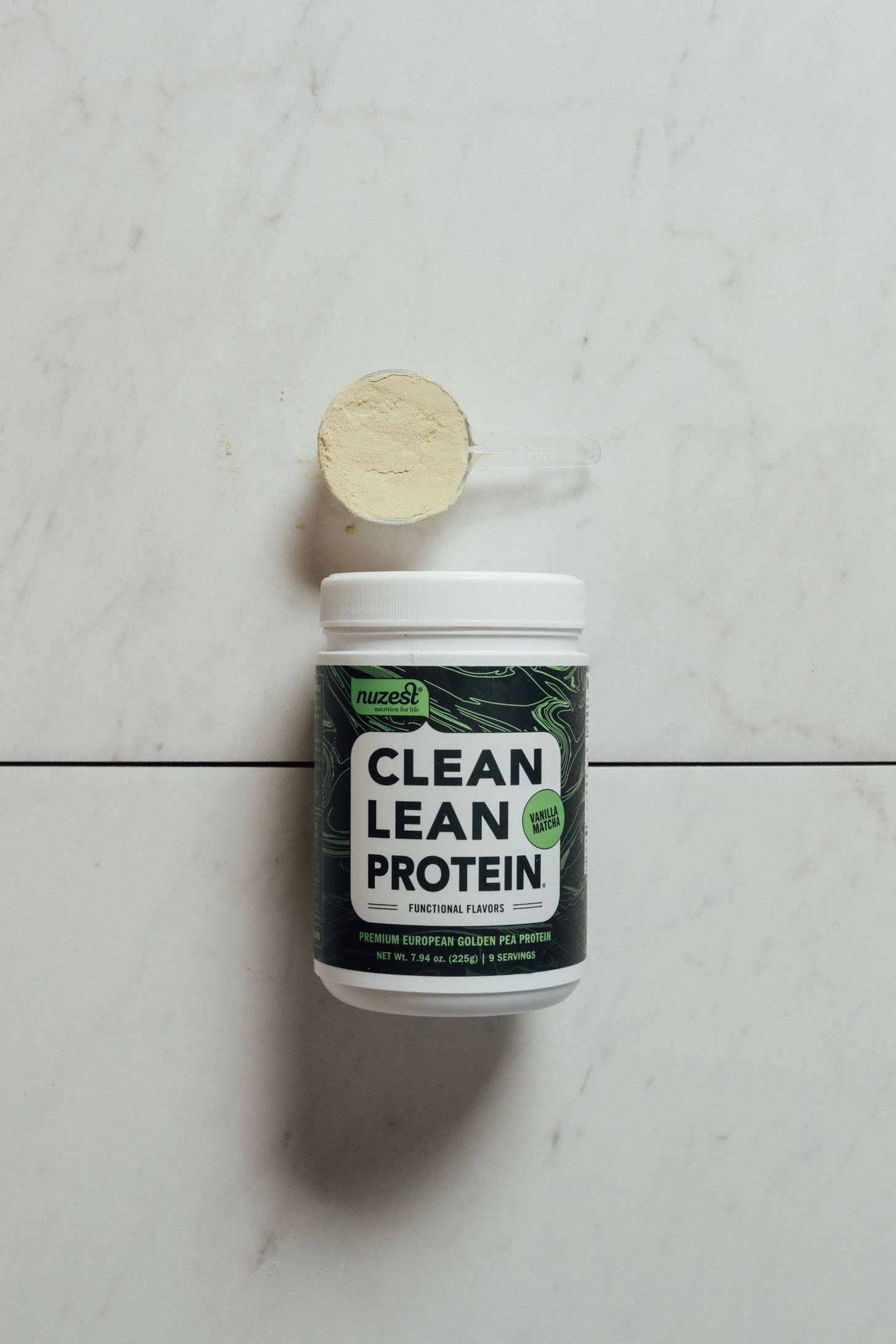 Tub and scoop of Nuzest Vanilla Matcha protein powder for our review