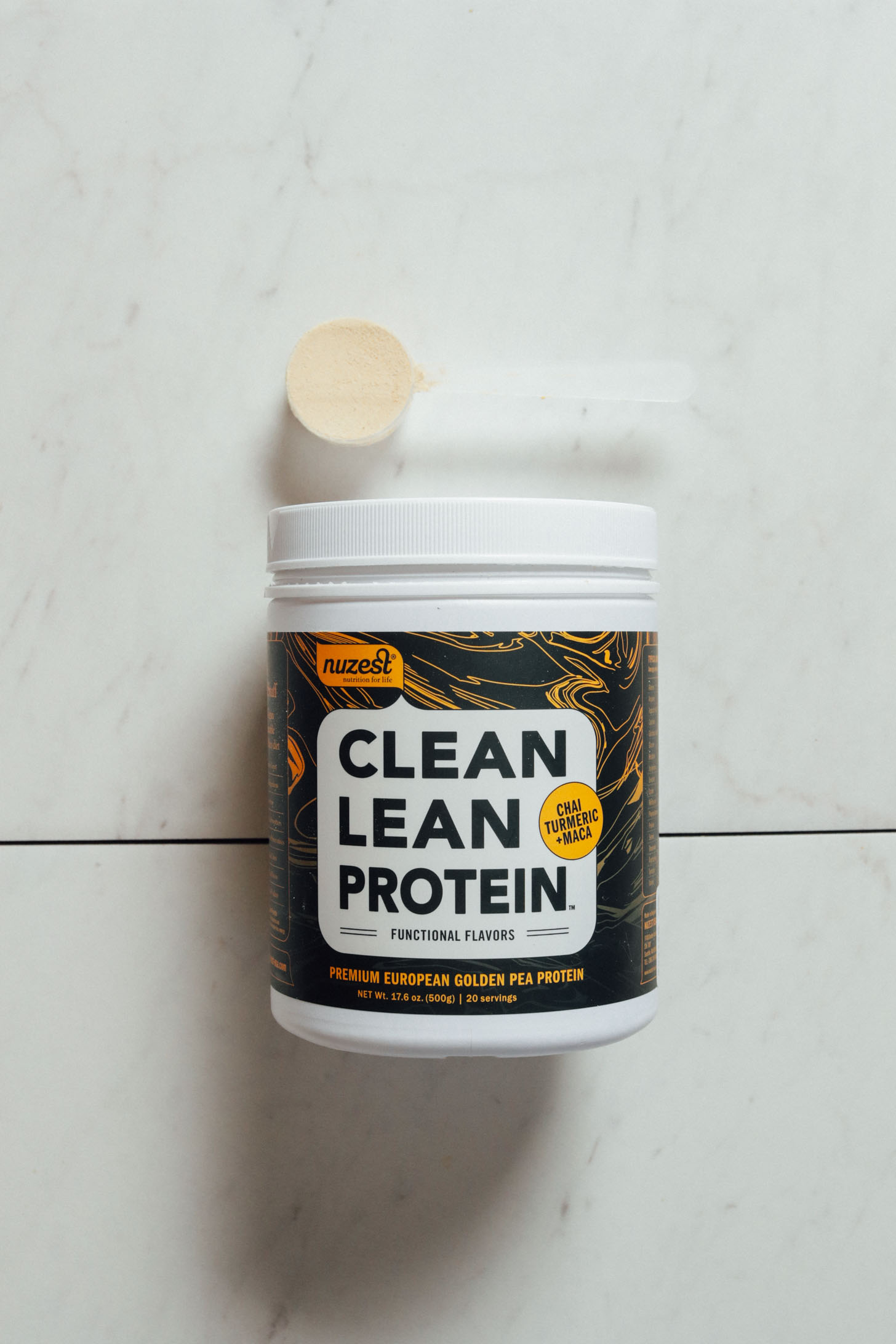Tub and scoop of Nuzest Clean Lean Chai Turmeric Maca protein powder