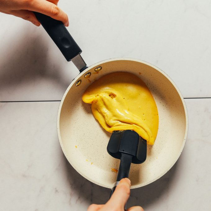 Using a rubber spatula to cook a vegan egg in a nonstick pan