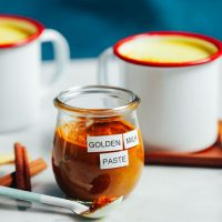 Jar and mugs of simple and delicious homemade golden milk