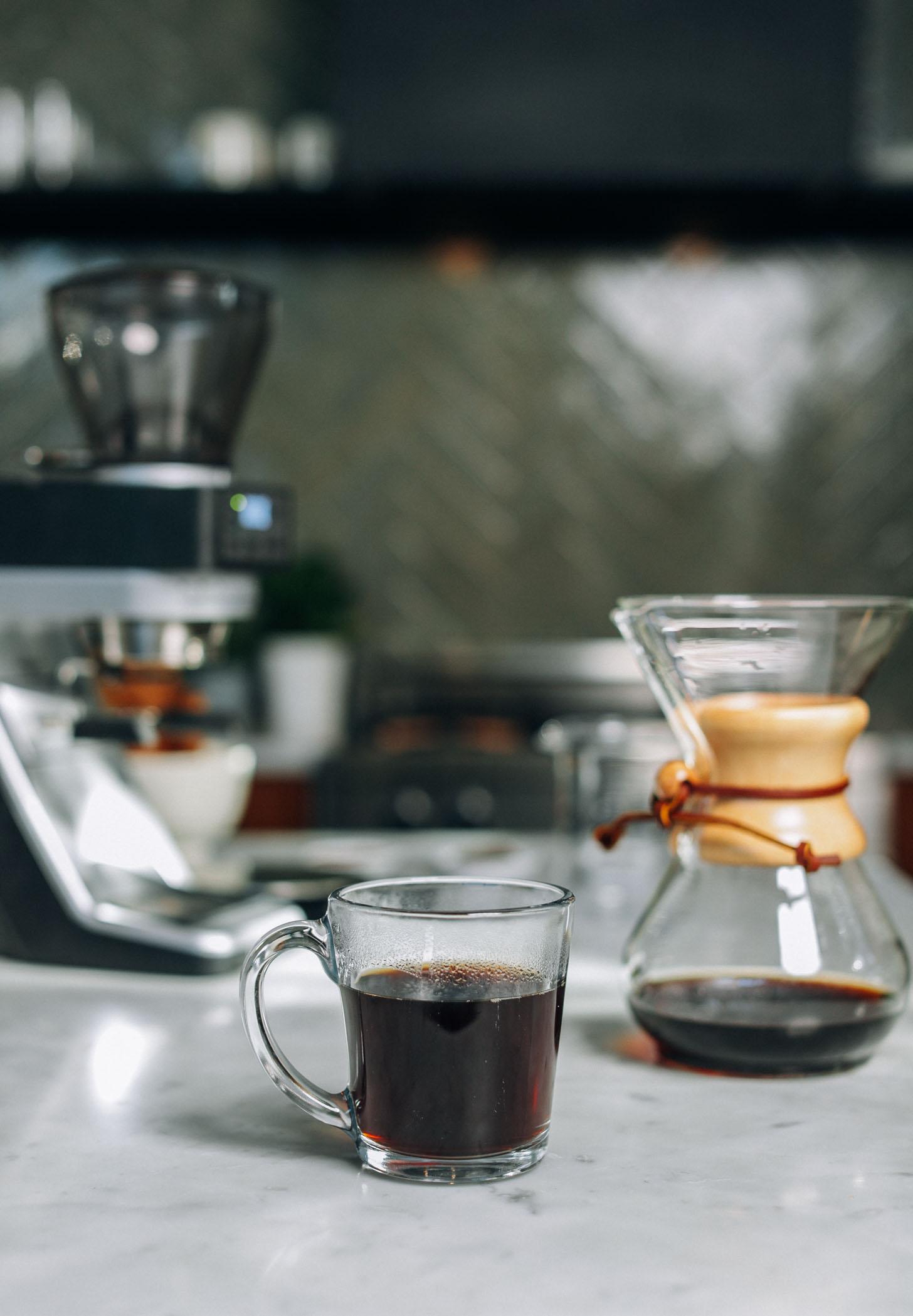 Coffee grinder, mug of coffee, and drip coffee maker