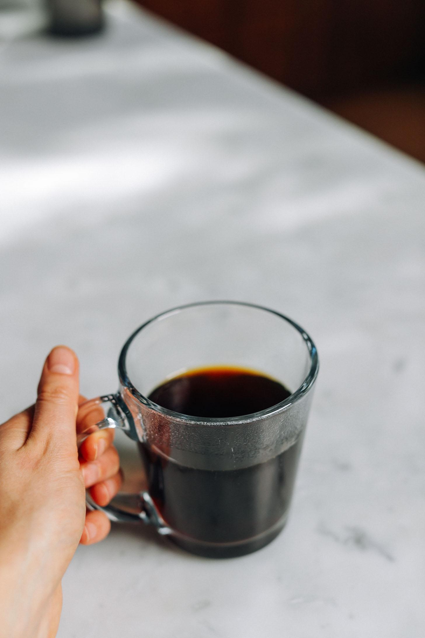 Holding the handle of a mug of coffee