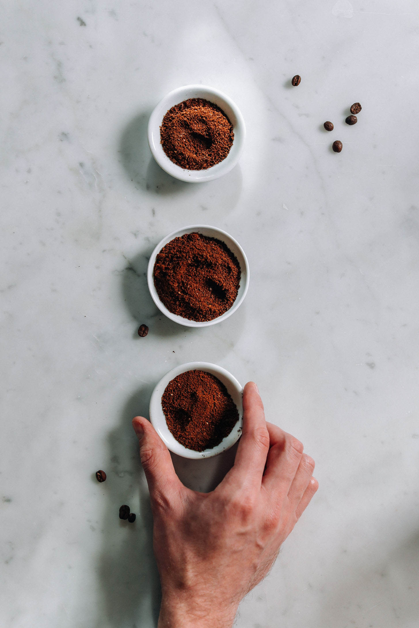 Three small dishes with ground coffee in them