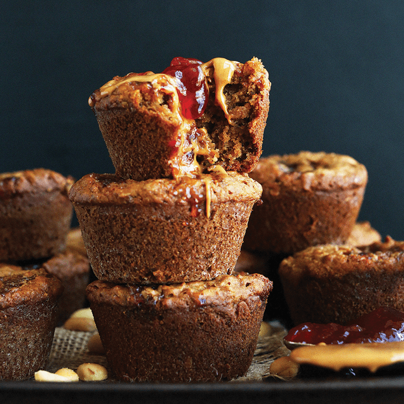 Spoonfuls of peanut butter and jelly next to a batch of PB&J Muffins