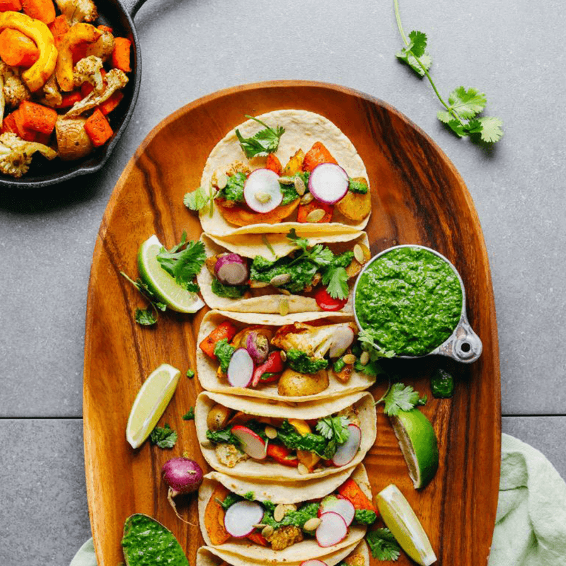 Wood platter of Roasted Vegetables Tacos with fresh cilantro and chimichurri