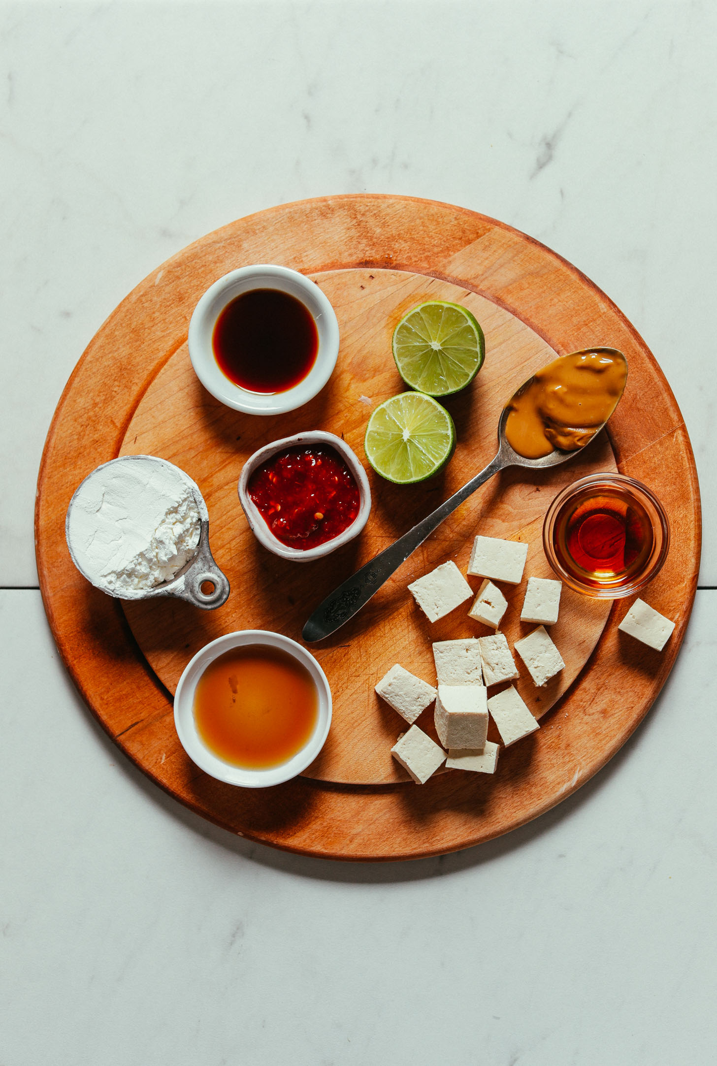 Wood cutting board with ingredients for making our Quick & Easy Peanut Tofu recipe