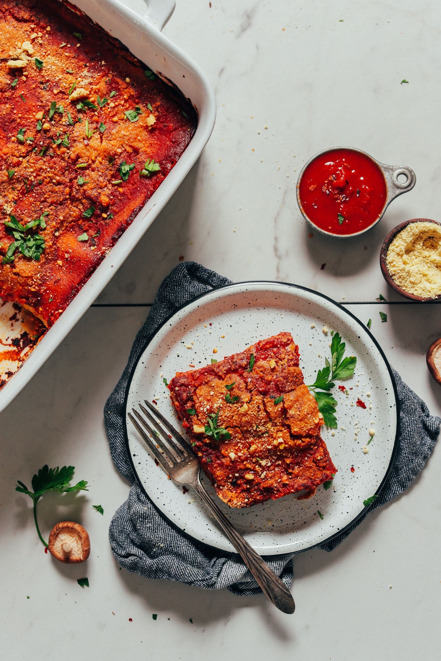 Slice of Vegan Lasagna alongside marinara, Vegan Parmesan, and the rest of the batch of lasagna