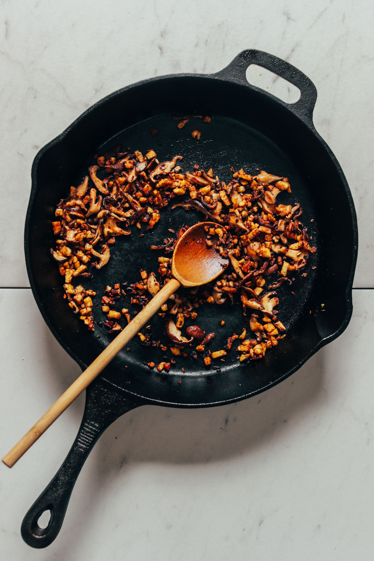 Using a wooden spoon to sauté mushrooms and tempeh in a cast-iron skillet