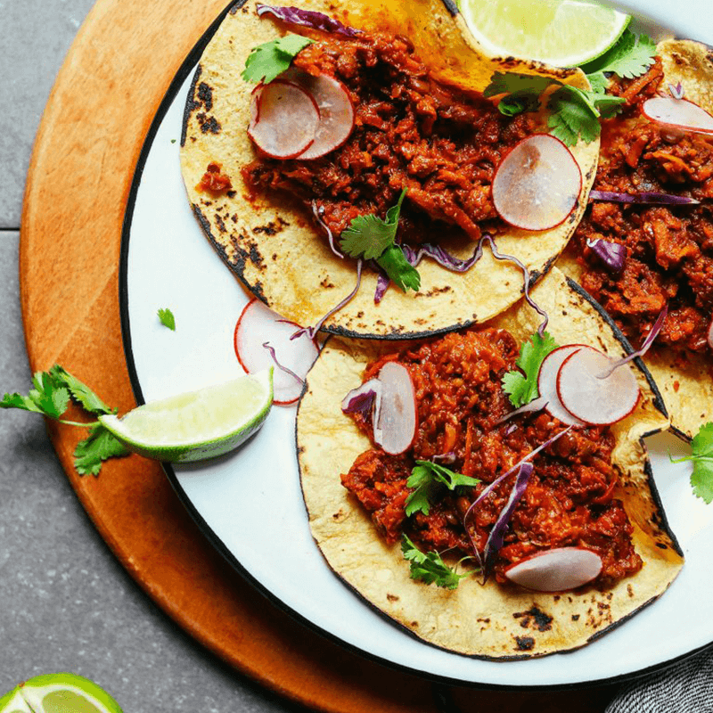 Plate of three Vegan Barbacoa Tacos topped with radish, cilantro, and cabbage