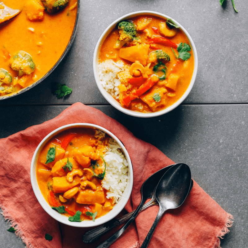 Bowls of rice and yellow Pumpkin Curry with cashews