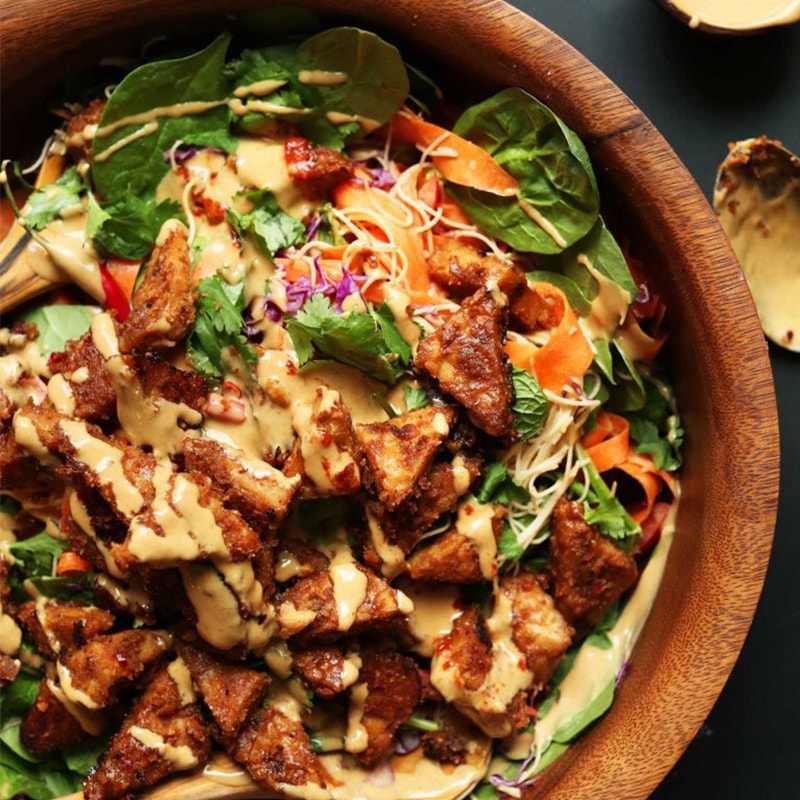 Wood bowl of Thai Salad with Marinated Peanut Tempeh