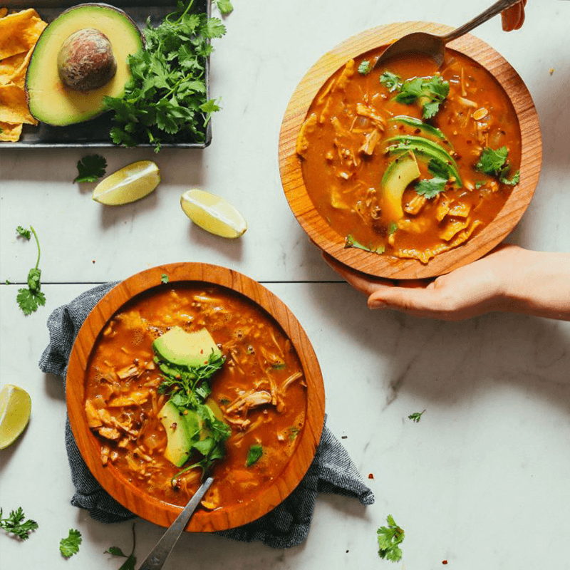 Using a spoon to scoop up a bite of our delicious Vegan Tortilla Soup made with jackfruit