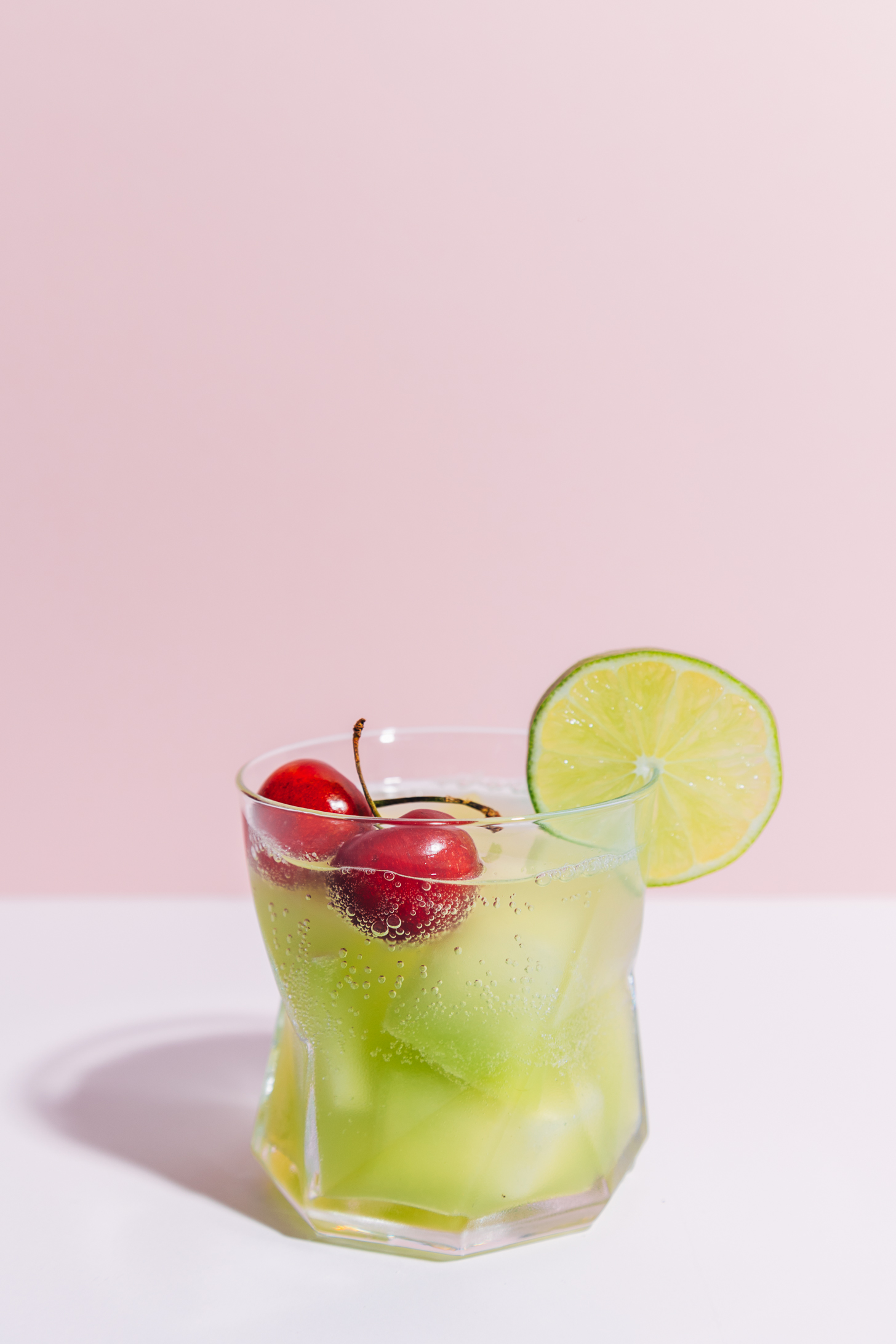 Glass of our Citrus and Melon Spritzer recipe garnished with fresh cherries and a lime slice