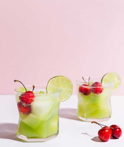 Two glasses of our Citrus & Melon Spritzers with fresh cherries in the glasses