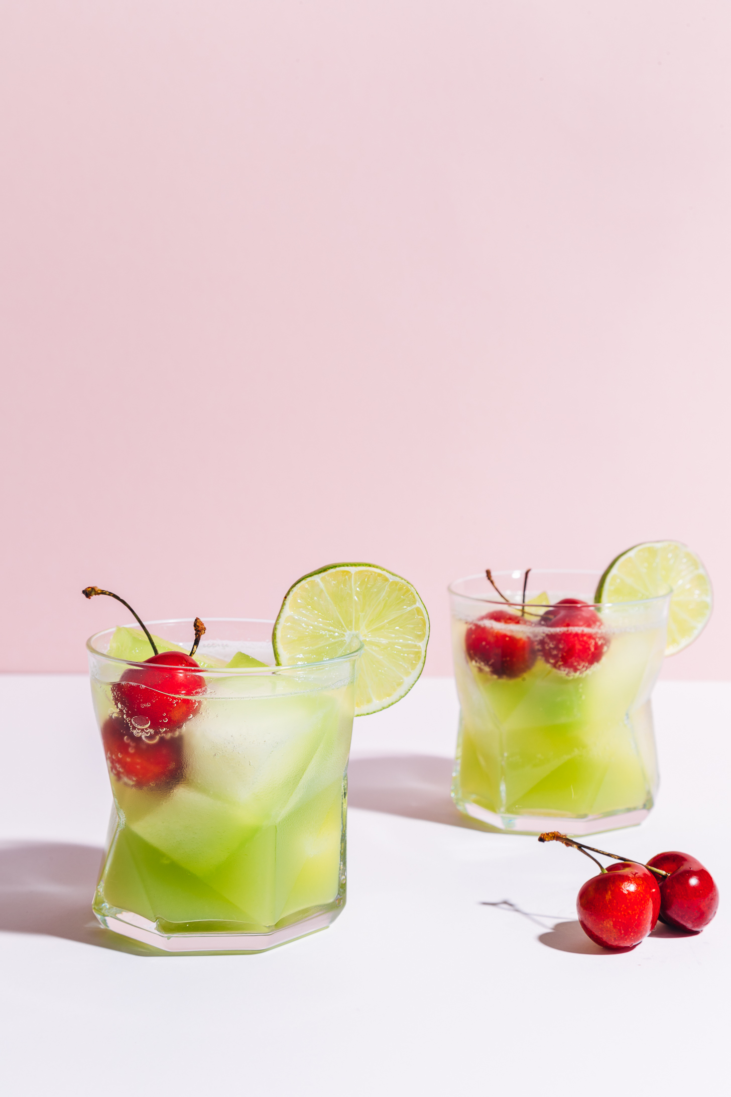 Two glasses of our Citrus & Melon Spritzer with fresh cherries in the glasses