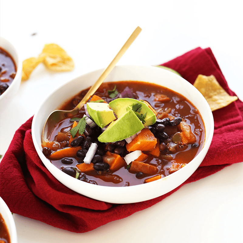 Tortilla chips beside a bowl of Sweet Potato Black Bean Chili topped with avocado