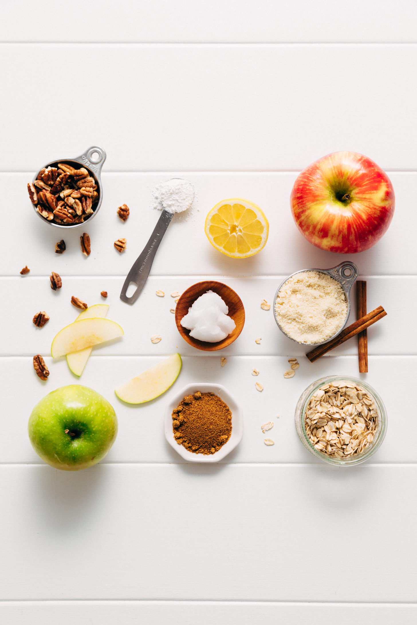 Assortment of ingredients for making our Healthified Apple Crisp recipe with almond meal, oats, and pecans
