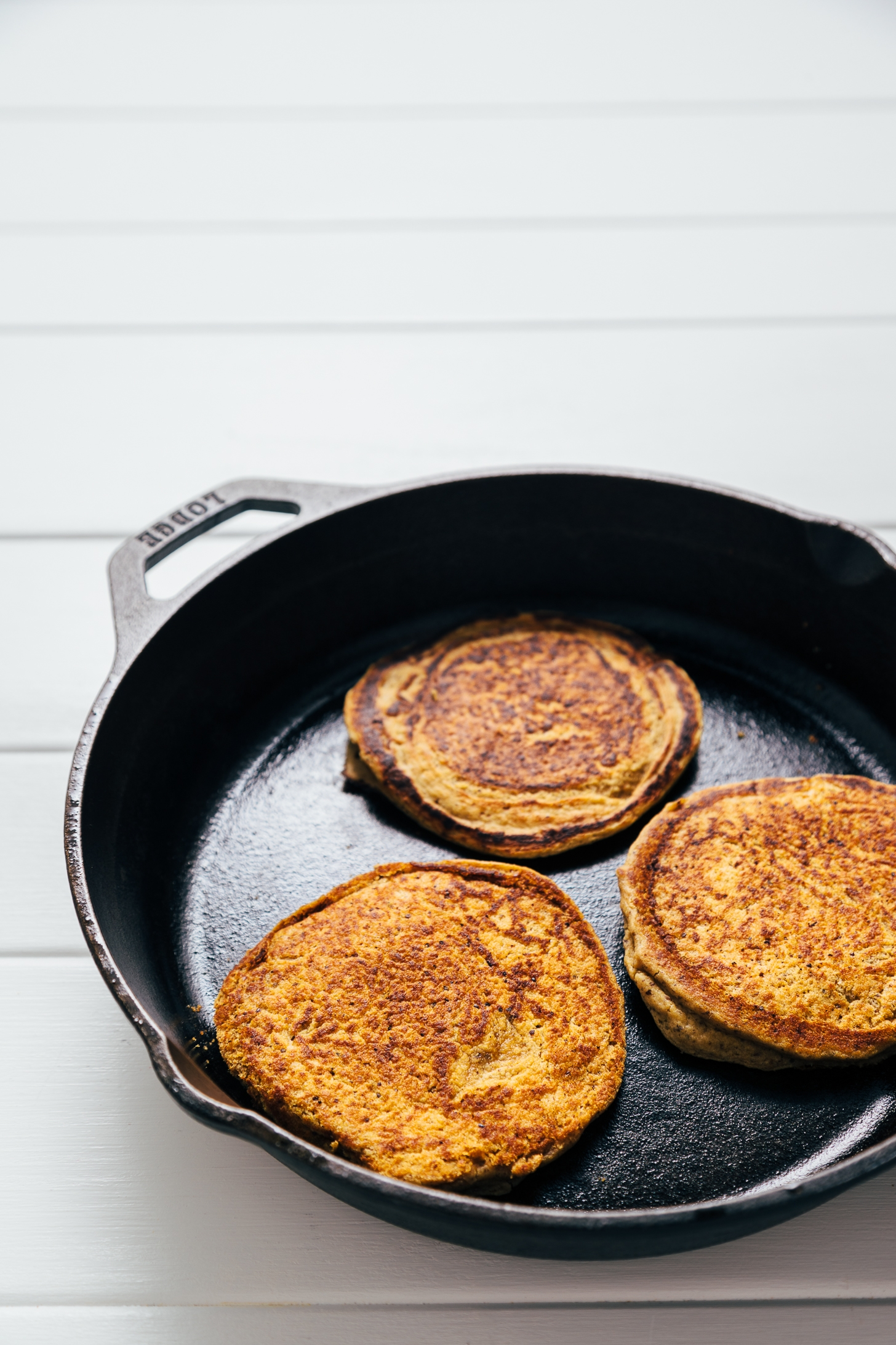Cooking vegan Peanut Butter Protein Pancakes in a cast-iron skillet