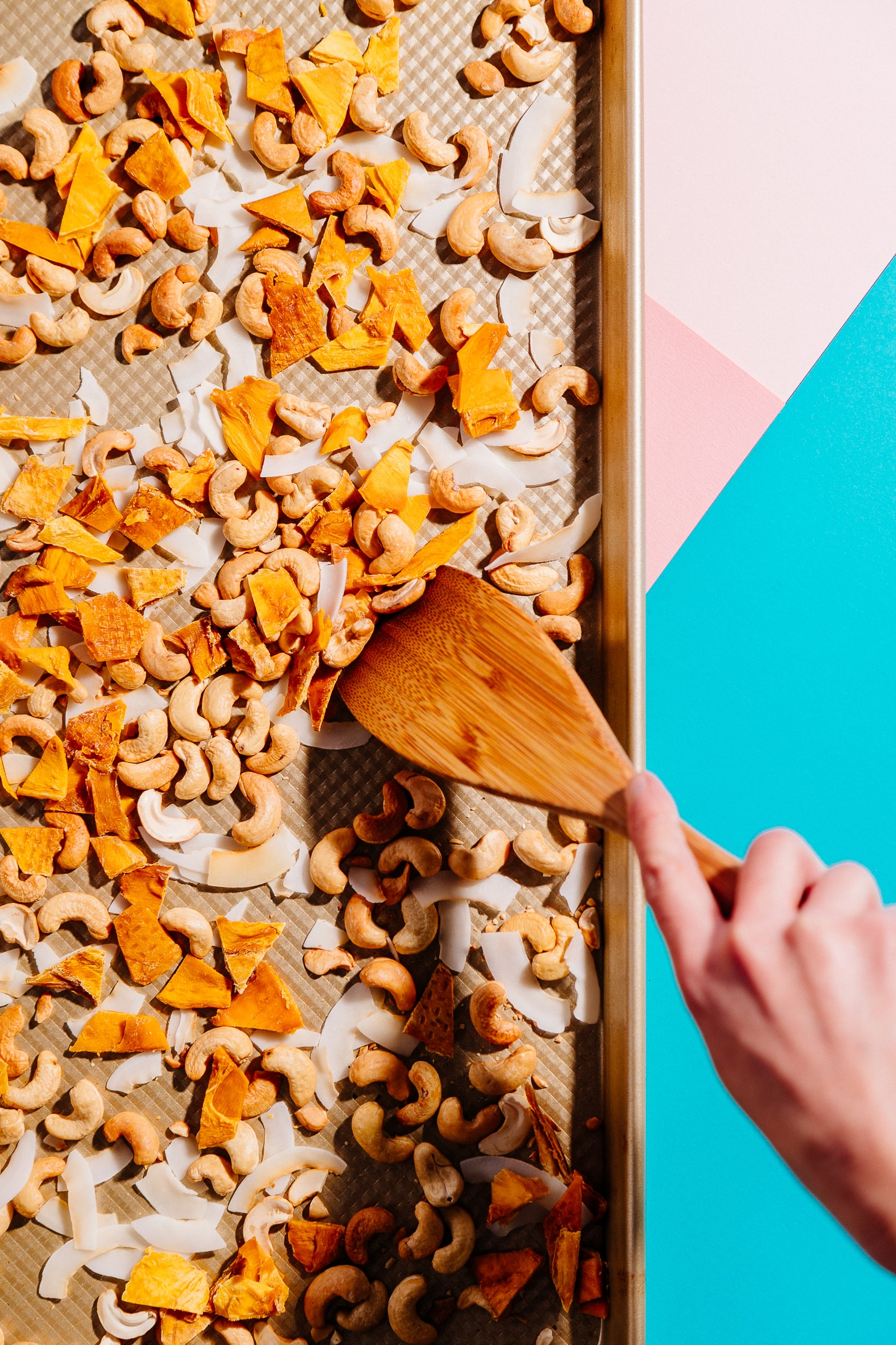 Using a wood spatula to mix healthy homemade Tropical Trail Mix on a baking sheet