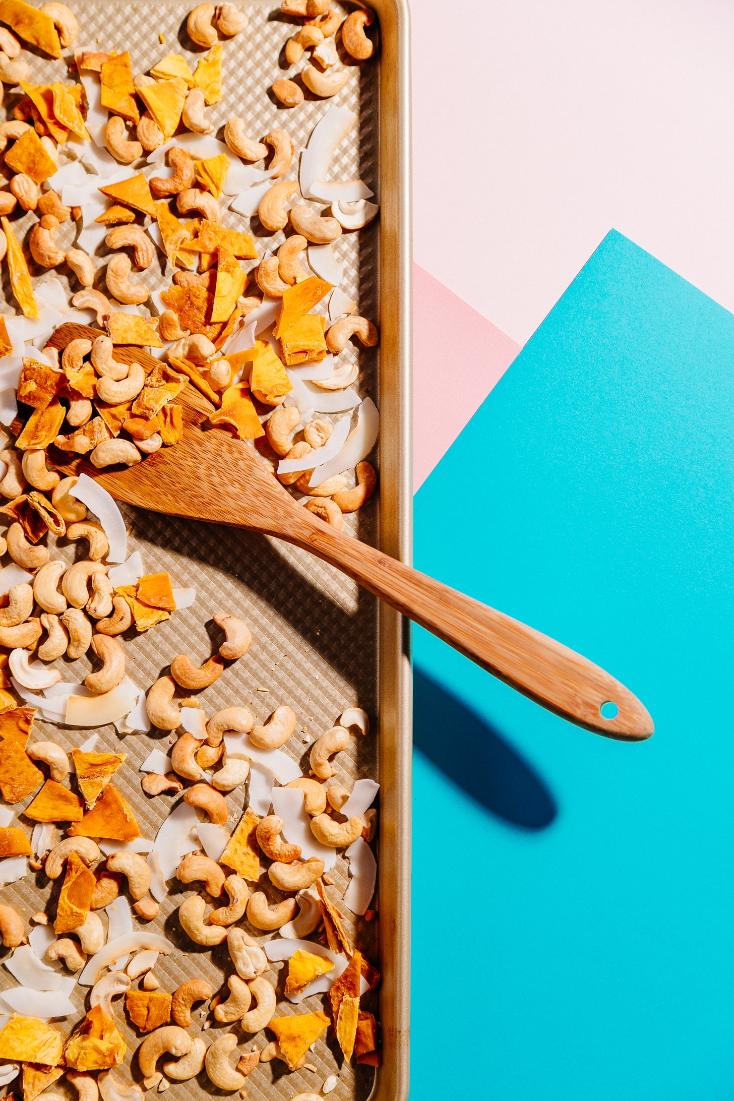 Wooden spoon resting on a baking sheet of healthy homemade Tropical Trail Mix