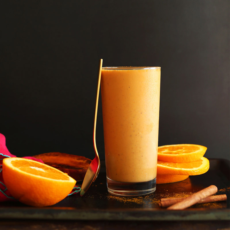 Tall glass of our healthy orange smoothie as part of our roundup of Delicious Uses for Roasted Vegetables