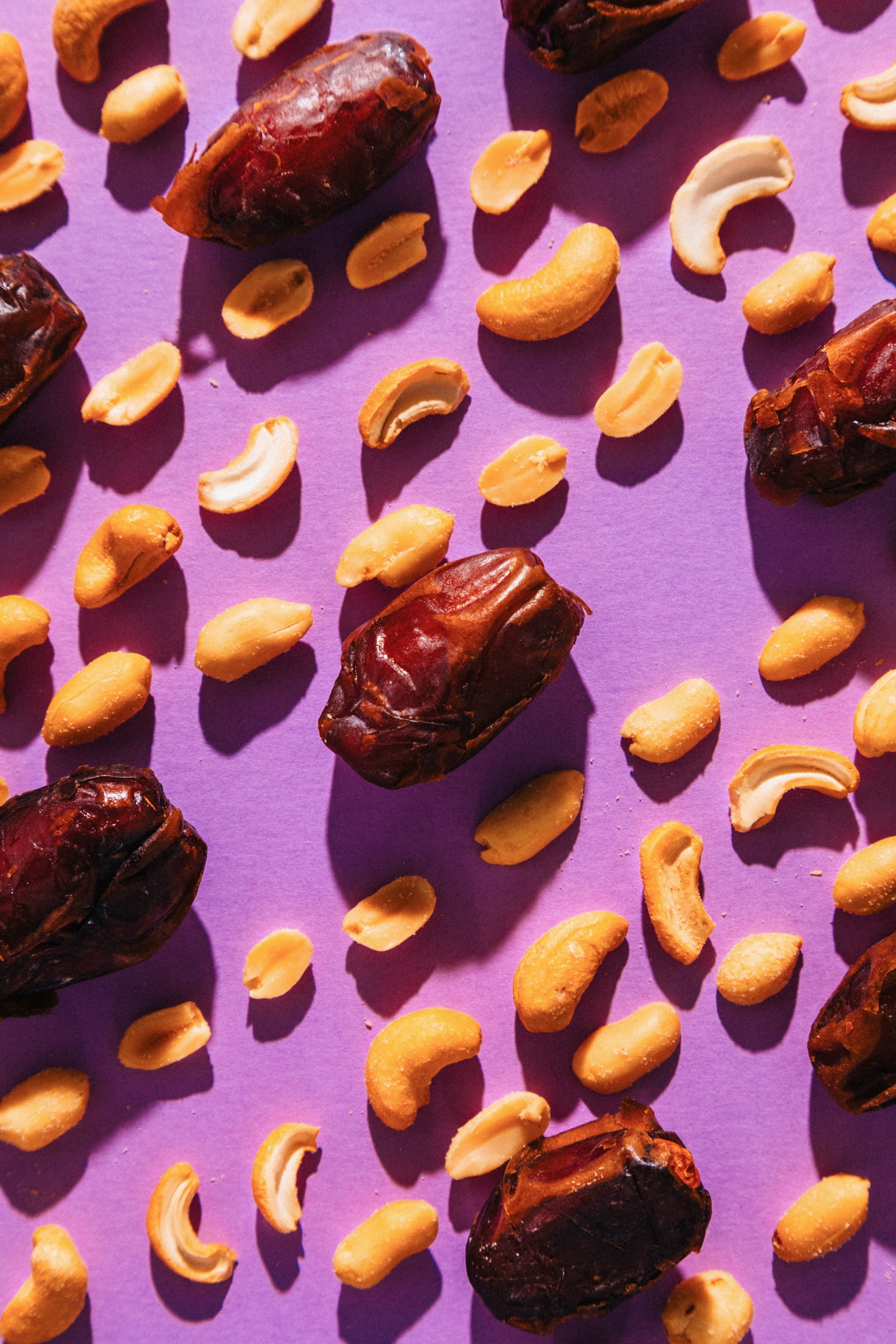 Dates, cashews, and peanuts on a purple background for making our PayDay Candy Bar Recipe