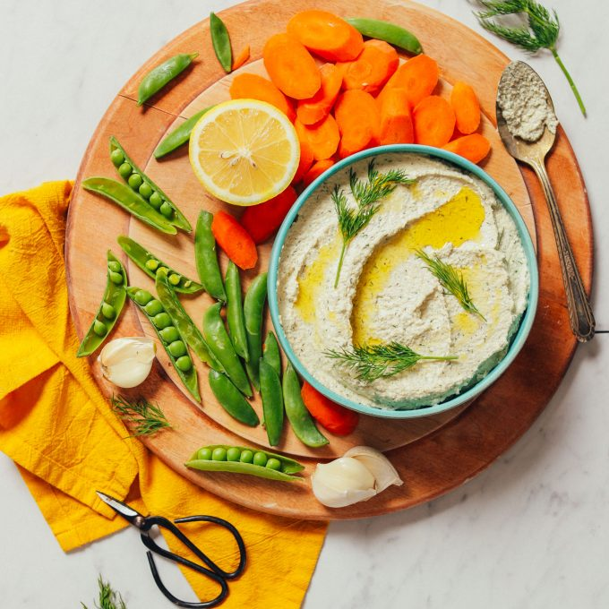 Bowl of Garlic Dill Sunflower Dip surrounded by fresh vegetables