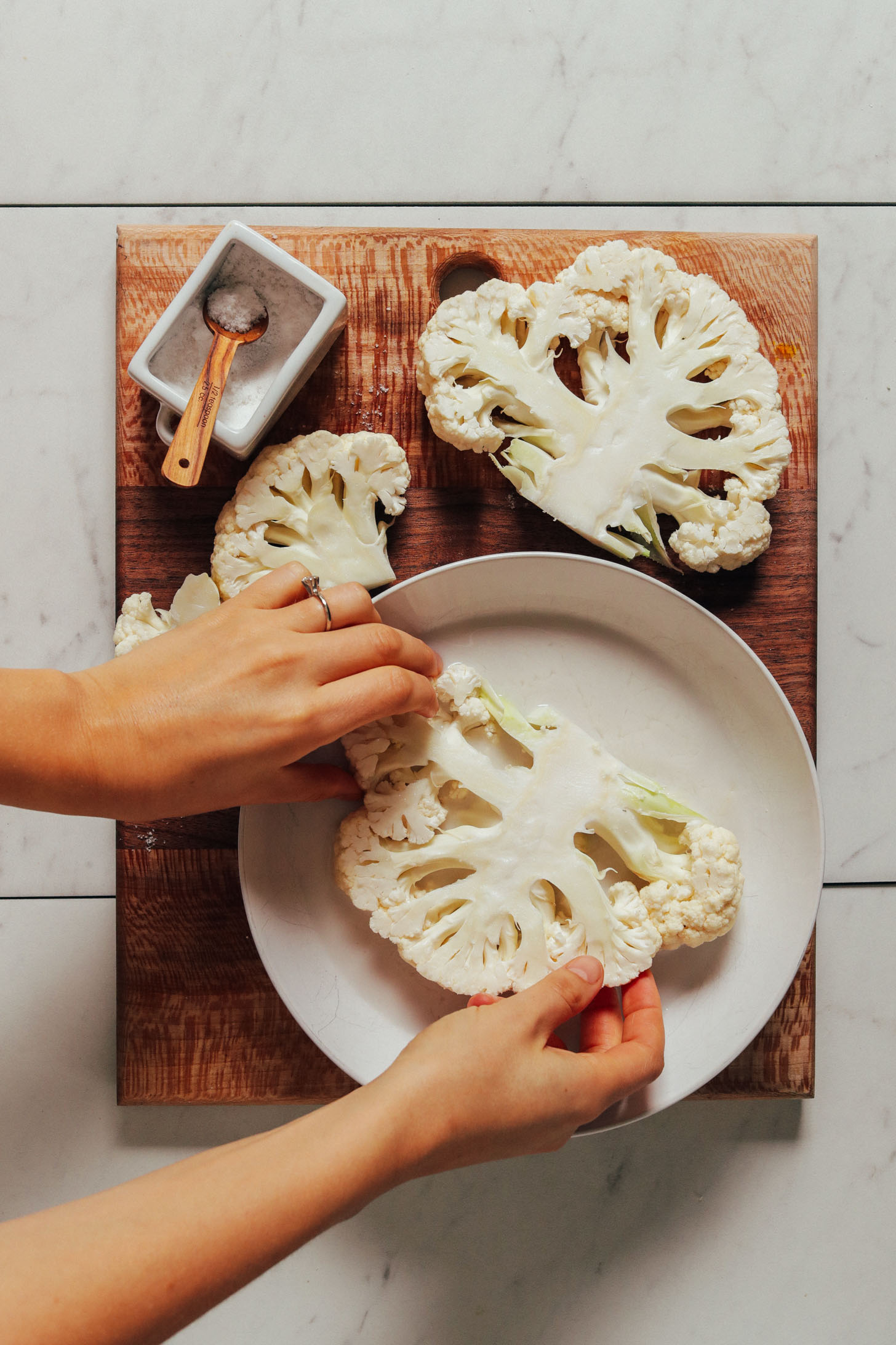 Coating cauliflower in a bowl of dairy-free milk before dipping in crust batter