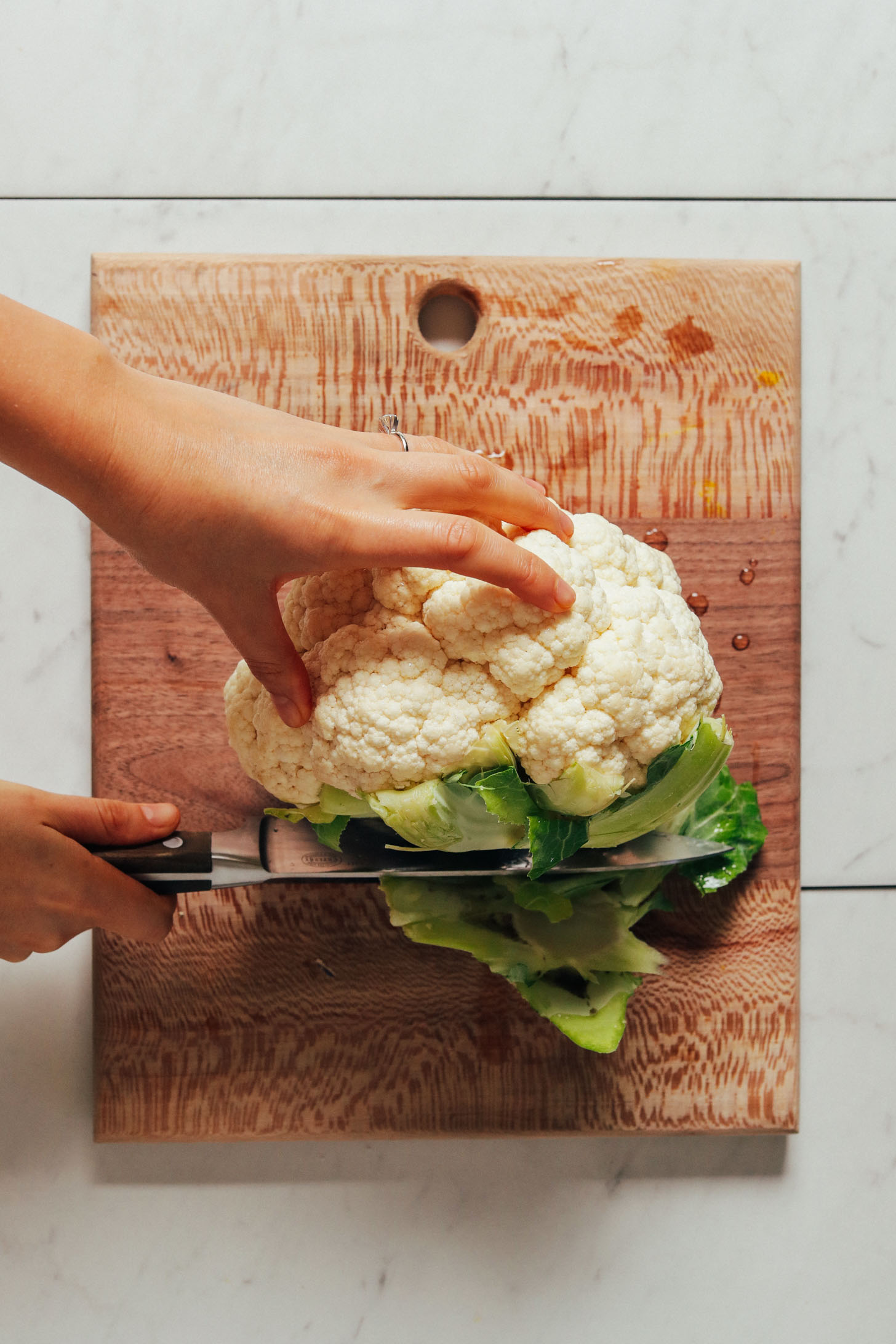 Slicing the stalky portion off a head of cauliflower