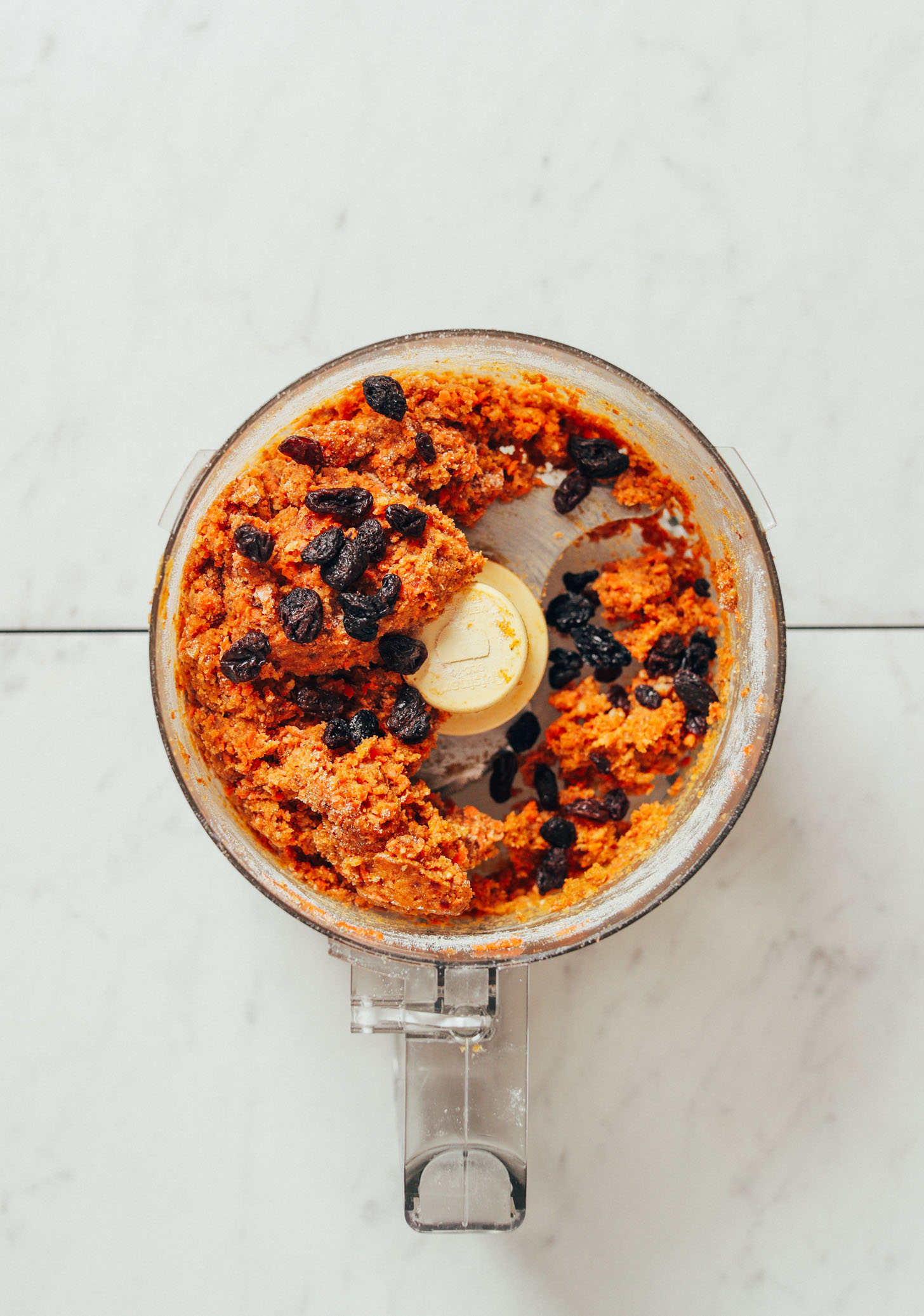 Food processor with Raw Carrot Cake Bite batter topped with raisins